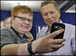 Republican presidential candidate Ohio Gov. John Kasich smiles as a supporter takes a selfie at a campaign event on Wednesday in Wauwatosa, Wis.