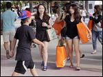Tourists from Taiwan carry shopping bags as they walk along a pedestrian area featuring retail shops and restaurants in Miami Beach, Fla. Consumer spending is credited for a slightly faster rate of growth in the fourth quarter than had been estimated.