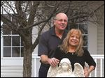 Mark and Jody Stoner stand behind a cement angel outside of their Perrysburg home. The couple bought the angel to look after Jody when Mark was out of town.