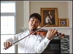 Sean Park, 16, plays his violin at home. He is co-concertmaster for the Toledo Youth Orchestra philharmonic and plays tennis and is on the debate team at Southview.