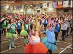 Bowling Green State University students Whitney Shemwell, of Louisville, Ky., center, and Ashley Ferguson of Hudson, Ohio, right, stay on their feet with hundreds of dancers during a 24-hour charity dance marathon Saturday to Sunday.