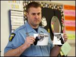 Toledo Police Officer Joe Okos shows third graders at McKinley Elementary photos of real and fake firearms.