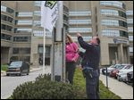 Kristin Calkins, trauma director at the University of Toledo Medical Center, the former Medical College of Ohio Hospital, and UT police Officer Mike Mattimoe raise a flag denoting April is 'National Donate Life' month.