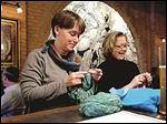 Carol Cierniak, left, and Laura Frailey knit and drink beer at the Black Cloister Brewing Co. bar in downtown Toledo.