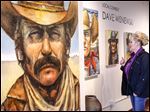 Tracy Miller of Sylvania, looks at the 'Cowboys and Indians' exhibit by local artist Dave Wisniewski at the River Centre Gallery in Sylvania. His work will be shown until May 2.