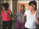Karen Everage, right, of Studio Fitness, gives a Zumba demonstration to Lenora McGlown, left, and Rochelle Kimble. Zumba demonstrations are planned at the Minority Health Summit at Robinson Elementary School.