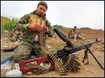 A volunteer with Popular Mobilization prepares his weapon in a military operation launched by Iraqi Security forces and allied Popular Mobilization forces to  regain con-trol of a town 180 miles north of Baghdad held by Islamic State in Iraq and Syria.
