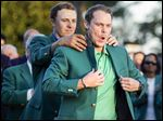 Defending champion Jordan Spieth helps 2016 Masters champion Danny Willett put on his green jacket following the final round on Sunday. Spieth gave away a six-shot lead in a three-hole span on the back nine.