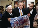 Ohio Gov. John Kasich looks at a picture of the White House made by students at a religious school in Brooklyn during a stop Tuesday, when Mr. Kasich's campaign for the Republican presidential nomination turned more aggressive.