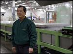 Charles Kim stands in front of the steamer at NOX Corp.