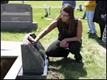 Brittany Stork, 34, of Perrys-burg touchesher late mother's monument. The remains of Dana Rosendale were exhumed for the second time on Friday in preparation for the retrial of Russell Adkins, who has been accused of killing her.