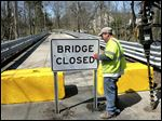 Chris Parcher of the Toledo Division of Transportation erects a sign at the east end of the Marengo Street bridge. The city on Friday closed the bridge indefinitely because of its deteriorating condition. A senior engineer says the soonest it can open is in 2019.