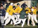 Clay's Jon Quinlan, second from right in helmet, is swarmed by his teammates after hitting the winning double to defeat St. John's.