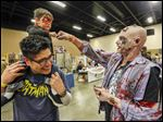 Above, Oliver Saenz, 2, sits on the shoulders of his dad, Fernando Saenz of Northwood, and bumps Jon Brown of Whitehouse, dressed as a zombie, at Fantasticon.