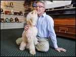 Shawn Diller, funeral director at Maison-Dardenne-Walker Funeral Home, gets a kiss from Zoey, a 6-month-old miniature golden doodle. But Zoey's affection goes far beyond Mr. Diller, offering her warmth and comfort to the grieving families who come through the door.