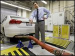 John Swanton of the California Air Resources Board explains how a Volkswagen Passat with a diesel engine is evaluated at the emissions test lab in El Monte, Calif. VW has agreed to a compensation deal over its cheating on the tests.