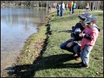 Sylvania resident Chad Dankert helps his 3-year-old son Connor reel in his line during the Kid's Trout Derby at Olander Park.