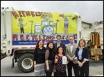 Sofie Abowd, front, stands with, from left, Jen Archer, executive director of the Sylvania Community Arts Commission; her parents, Jemma and Michael Abowd; Chris Jones, general manager of Republic Services, and Karen Hehl, principal at Central Trail Elementary, in front of the truck that bears Sofie's 'Recycling Rocks!' design.