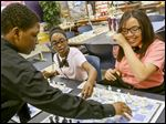 Nia Thomas, 12, center, and Ylisia Crawford, 15, with teammate Aoveon Gould, 13, set up their boards during Chess Club at Jones Leadership Academy in Toledo. Nia had never played chess before she joined the club in September.