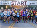 A crowd of 6,000 people bolt from the starting line at the Mercy Health Glass City Marathon in downtown Toledo. The runners logged anywhere from 3.1 miles in the 5k or the marathon's full 26.2 miles.