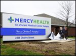 Sister Dorothy Thume, senior vice president of mission and values integration, left, Dr. Imran Andrabi, president and CEO of Mercy Health Toledo, and Mayor Paula Hicks-Hudson unveil a sign that ushered in a new name Tuesday for Mercy Health, formerly known as Mercy.