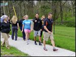 Above, David Espinoza, track and cross-country coach at Lourdes, leads the 'Walk a Mile in Her Shoes.'
