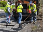 City workers Jeff Viertlbeck, Ben Johnson, and Pat Murawa, from left, fill in potholes on Kenwood Boulevard. Crews are spending three days trying to catch up on the backlog.