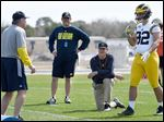 Michigan's coach Jim Harbaugh, kneeling, watches defensive coordinator Don Brown, left, work with Cheyenn Robertson in Bradenton, Fla. on Feb. 29.  A little over a month later, the NCAA ruled the camps illegal and ordered schools to stop.