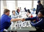 Charlie Mlcek ,13, left, from Anthony Wayne Junior High, and Anthony Stewart-King II, 14, right, from the Jones Leadership Academy, shake hands after their match during the 13th Annual Toledo Public Schools Elementary Chess Tournament at Beverly Elementary School on Saturday. Charlie won the game. Below, Anthony looks over his notes.