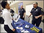 Toledo Police officer David Vasquez, right, speaks with Maleeka Kynard, 23, about joining the department during the annual youth job fair at the SeaGate Convention Centre.