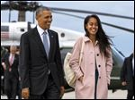 President Barack Obama jokes with his daughter Malia Obama as they walk to board Air Force One from the Marine One helicopter. The White House announced that Malia Obama will take a year off after high school and attend Harvard University in 2017.