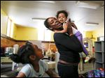 Nicole Barnes hugs daughter Camille Cain, 18-months, while playing with daughter Ta'Nyla Barnes, 5, at Family House. Ms. Barnes says knowing that her children learn while they are cared for will ease her mind as she rebuilds her life.