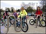 Bella Zadrazil, 6,  left; Cameran Keblesh, 7; Samantha Zadrazil, 8 (mostly obscured); Rebekah Zadrazil, 10, and Brylee Keblesh, 9, put their bikes up after riding to school. Students, parents, and volunteers biked to mark National Bike to School Day at Elmhurst Elementary School on Wednesday. The event is sponsored by Live Well Greater Toledo.