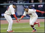 Cleveland Francisco Lindor, right, is congratulated by third-base coach Mike Sarbaugh after Lindor hit a three-run home run in the fifth inning — the biggest of his three hits against Detroit.