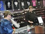 Mac Botek of Toledo, left, purchases vaping liquid from Assistant Manager Mark Detwiler at Vapors Electronic Smoke Shop in West Toledo. The FDA announced plans Thursday to begin regulating the e-cigarette industry.
