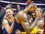 Cleveland Cavaliers' LeBron James (center) celebrates with Kyrie Irving, right, and Matthew Dellavedova after Game 4 of the Atlanta series.