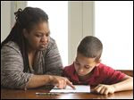 Debra Wilkins helps her son Jayden, 10, with his homework Tuesday April 26, 2016, in Toledo , Ohio. Jayden has fetal alcohol exposure and as a result requires  help in school.