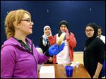 Ninth graders from the Toledo Islamic Academy,  Fatimah Aftab, second from left, Zainab Jaafar, and Sara Rashid, right, watch as  Claire Cohen, associate chemistry lecturer at the University of Toledo, front left, pulls a quickly frozen banana from dry ice. The girls were told of work in physics, astronomy, chemistry, biology, engineering, pharmacy, and medicine.