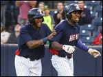 Toledo Mud Hens right fielder Wynton Bernard, right, celebrates hitting a three-run homer against the Louisville Bats with teammate Jordany Valdespin, left, during the sixth inning of the Hens' win.