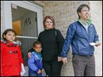 Mark Ohashi, right, executive director Habitat for Humanity of Wood County, dedicates a Habitat home to Brittany Periatt and her son Dante Jones, 4. Mr. Ohashi's daughter Anna Ohashi, 9, stands at left.