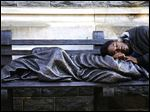 A homeless man sleeps next to the Homeless Jesus statue in Washington in this photo provided by the Methodist Central Hall. The statue has been accepted with open arms in other cities, including the Vatican, but has been rejected by the Westminster city council.
