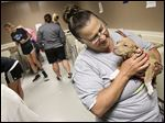 Monica Kernahan of Perrysburg gets acquainted with the 2-month-old 'pit bull' puppy she named Millie during the 'Bark in the Park' fund-raiser at the Toledo Area Humane Society's new shelter in Maumee.