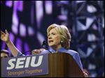 Democratic presidential candidate Hillary Clinton promises to crack down on gun violence and work on immigration reform as she speaks to members of the Service Employees International Union at its convention in Detroit on Monday.