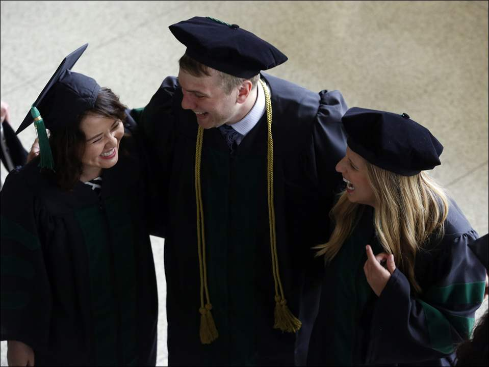 Dr. Anthony Canestraro, center, smiles with peers Dr. Phuong Cao, left, and Emily Campbell, right, while processing into the theater during the UT College of Medicine and Life Sciences commencement exercises at the Stranahan Theater on May 27, 2016.