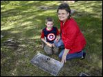 Becky Visser with her 9-year-old grandson Oliver, pose at the gravestone of Pfc. Raymond Manz. She has been researching the story of the soldier, who was killed April 30, 1945.