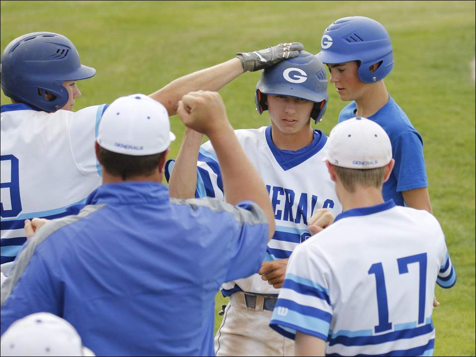 Anthony Wayne High School player Sean Mowery is greeted by teammates after scoring the Generals' only run against Cleveland St. Ignatius during their Division I regional baseball final.