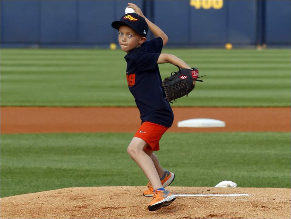 Carter Williams, 7, of Toledo, who was the eight-millionth fan at the stadium, throws out a ceremonial pitch.