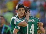 In a 2014 file photo, Mexico's Alan Pulido consoles teammate Javier Hernandez after a World Cup loss. A state official says that  Pulido has been kidnapped in the northern border state of Tamaulipas.