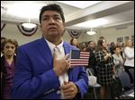 New United States citizens recite the Pledge of Allegiance during a naturalization ceremony in Hialeah, Fla.