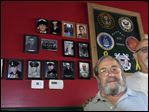 Veteran Bob Mericle, left, stands alongside bar owner Tim Muir in front of a tribute to veterans at Fat Jacks bar in Perrysburg. Mr. Muir said he is looking to fill the display with more photos of veterans. He said the wall has been a real conversation starter.